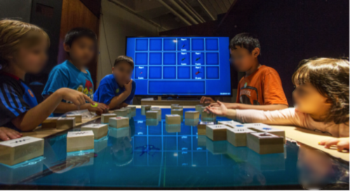Kids playing on the Oztoc table